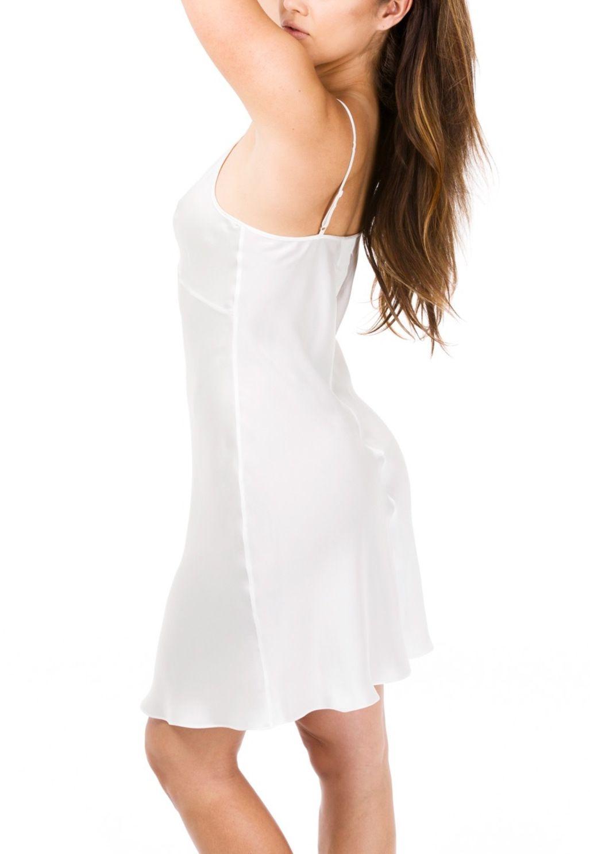 A woman wearing a white slip dress