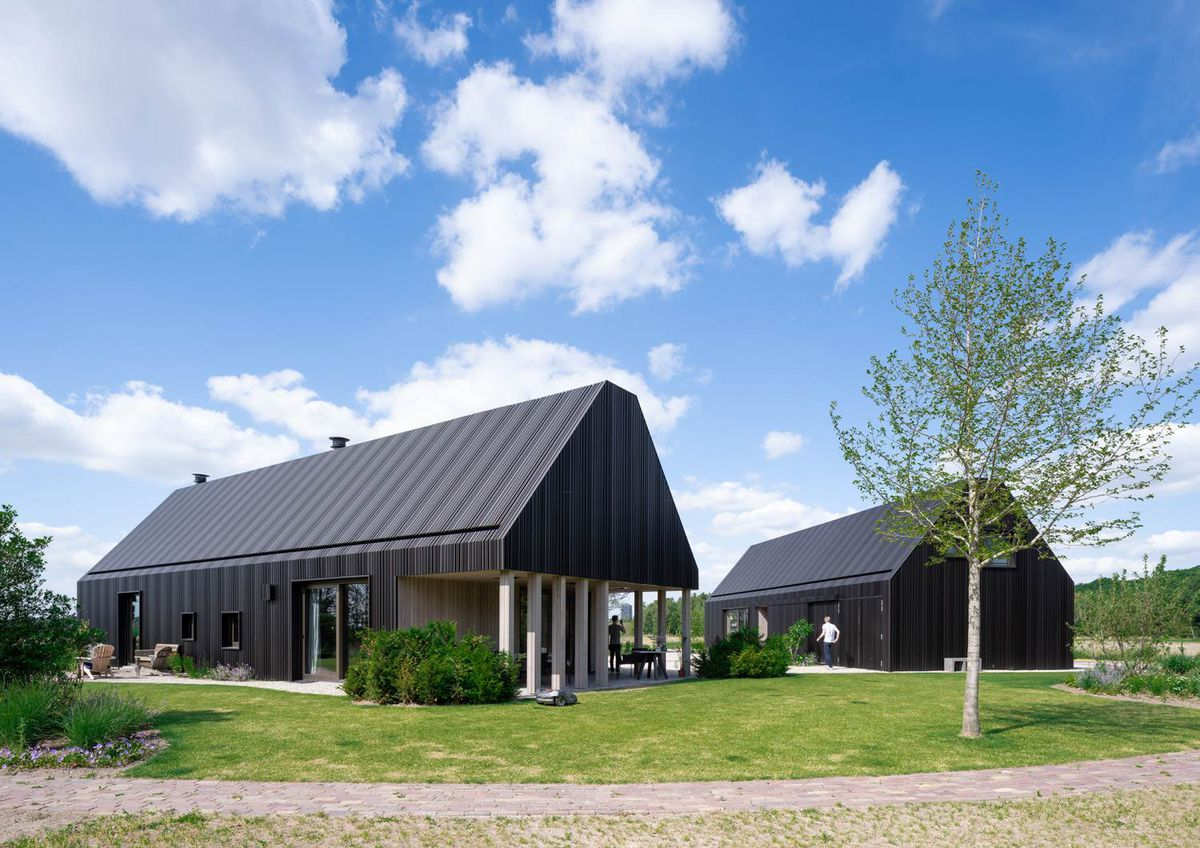 Two black clad structures next to each other. The one of the left has white columns, both look a bit like barns set in the grass.
