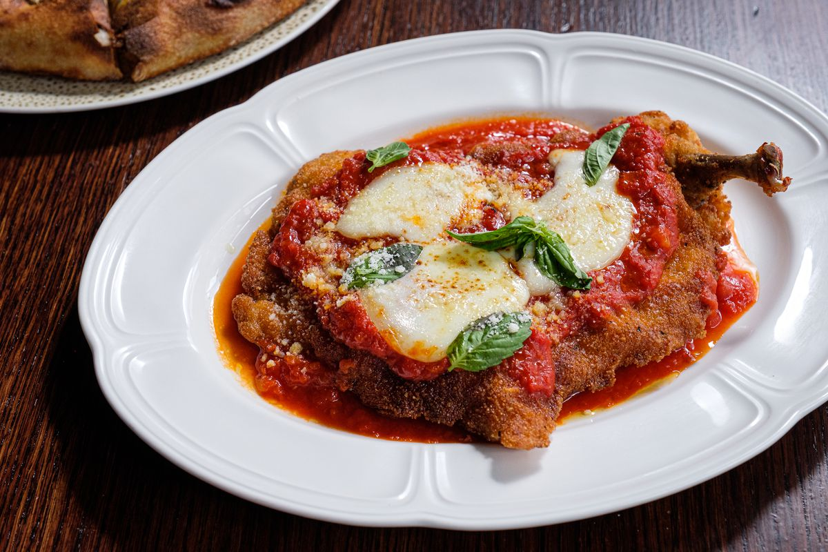 A round white plate holds a huge chicken parm