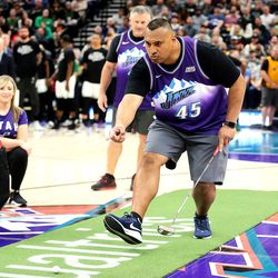 BYU head football coach Kalani Sitake tries to guide a golfball into the cup, as he and Utah head football coach Kyle Whittingham have a putting contest during a break in the game as the Utah Jazz and the Boston Celtics play an NBA basketball game at Vivint Smart Home Arena in Salt Lake City on Wednesday, Feb. 26, 2020. Boston won 114-103.