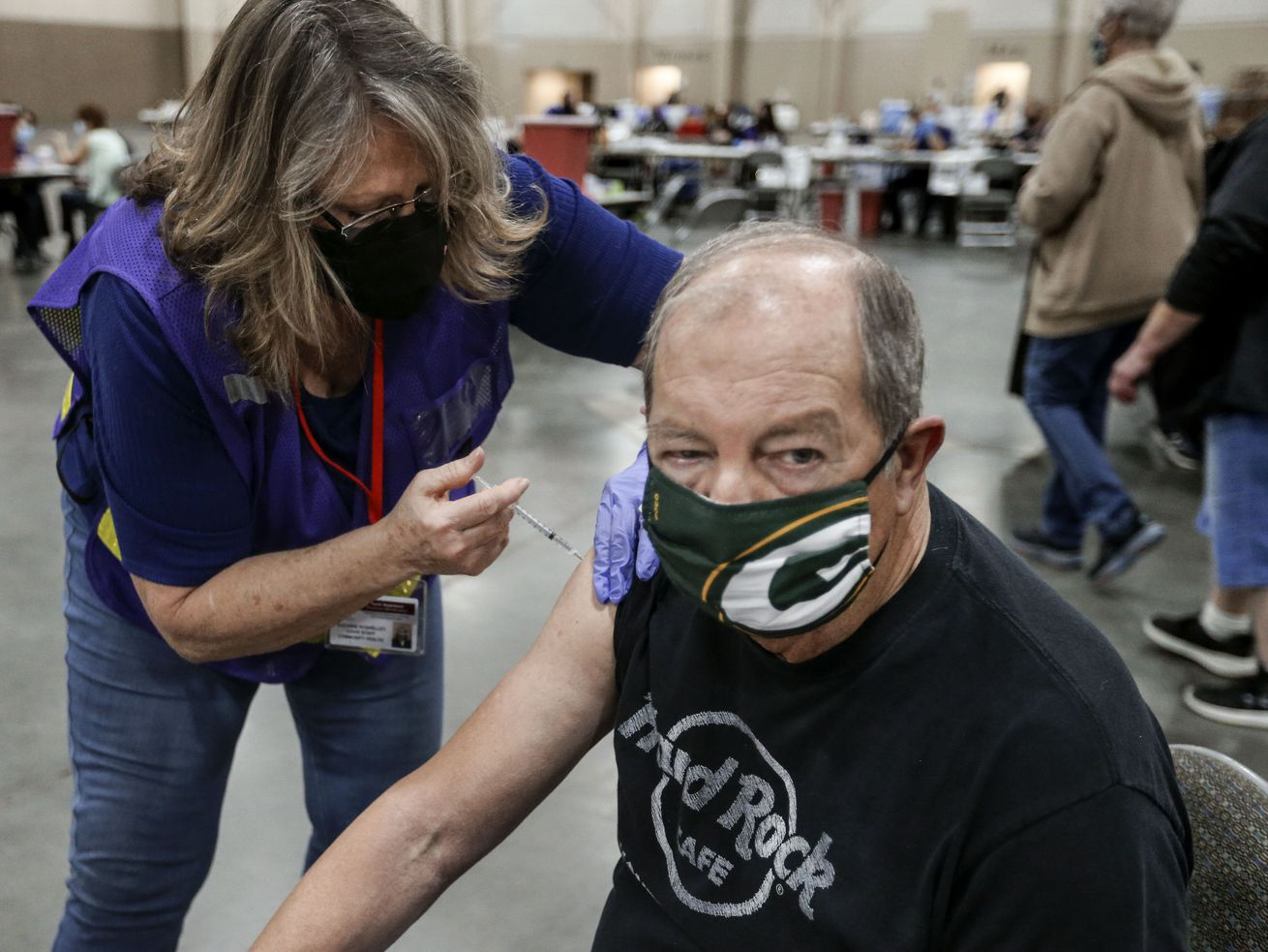 Suzanne Roskelley, left, gives Bob Olschesky, of West Valley City, a COVID-19 vaccination at the Mountain America Exposition Center in Sandy on Thursday, Feb. 11, 2021.