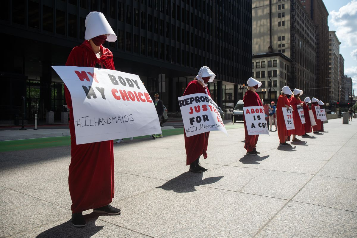 """Illinois Handmaids hold signs during the """"Bans Off My Body"""" rally, decrying Texas' new law that bans most abortions after six weeks into pregnancy, Friday afternoon at Federal Plaza in the Loop."""