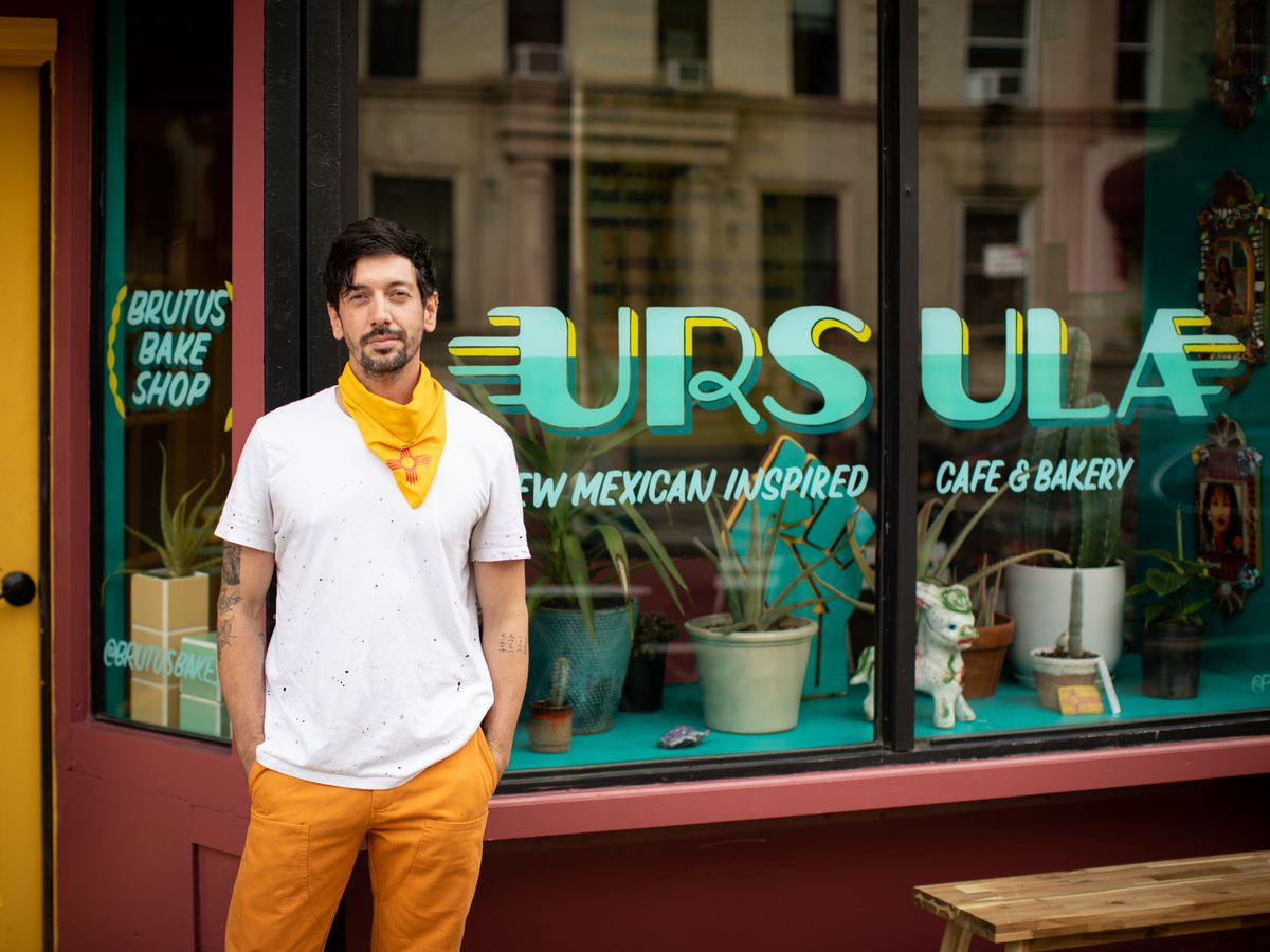 A man in a white shirt, yellow trousers, a yellow bandana stands in front of a restaurant