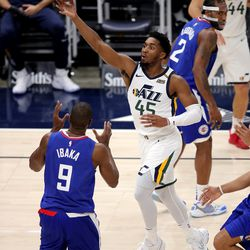 Utah Jazz guard Donovan Mitchell (45) floats the ball up an over LA Clippers forward Serge Ibaka (9) for a shot as the Utah Jazz and LA Clippers play in an NBA basketball game at Vivint Smart Home Arena in Salt Lake City on Friday, Jan. 1, 2021.