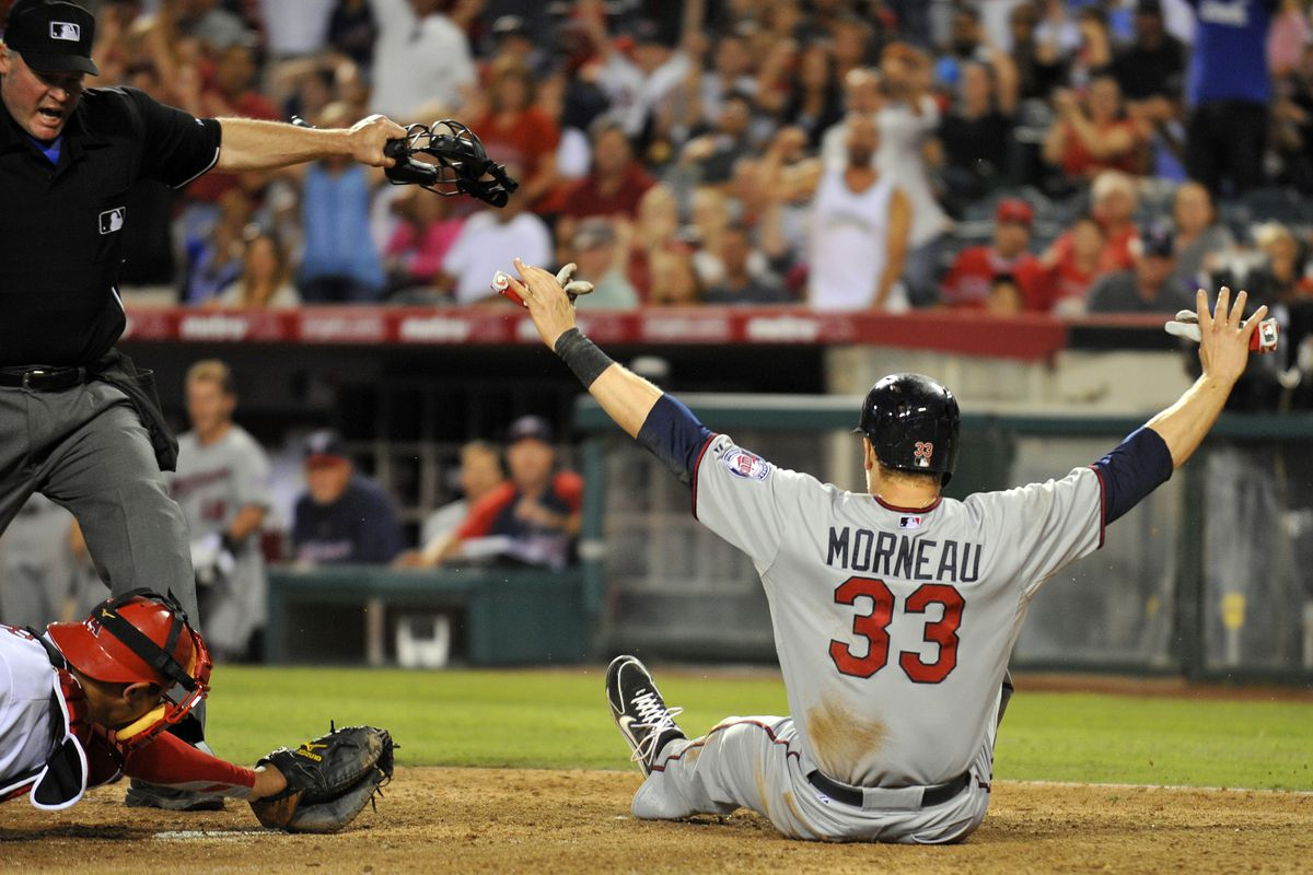 Justin Morneau celebrates his brilliant 8th inning home-plate slide--a highlight of the game.