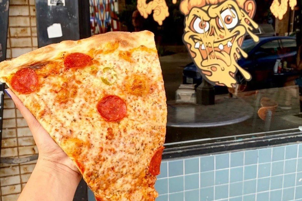 a hand holding a large slice of pepperoni pizza in front of a decorated window and blue-tiled wall