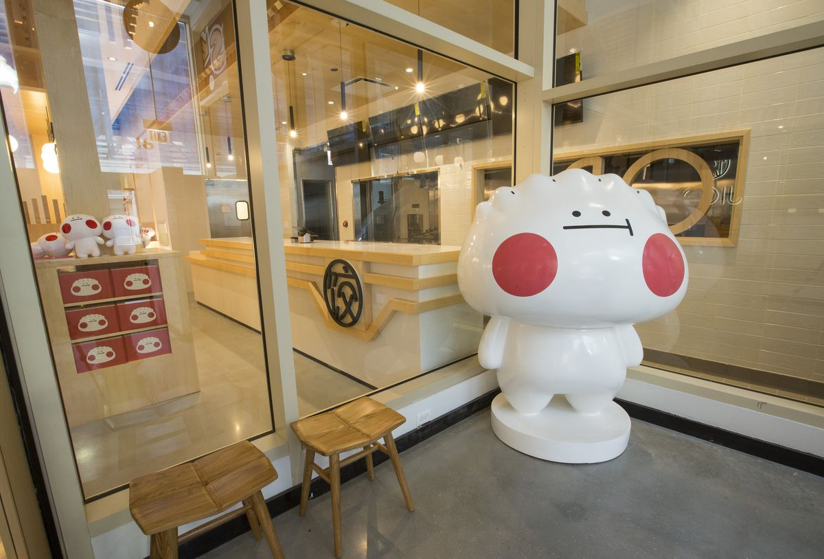 A Chinese restaurant's friendly mascot standing in front of its entrance.