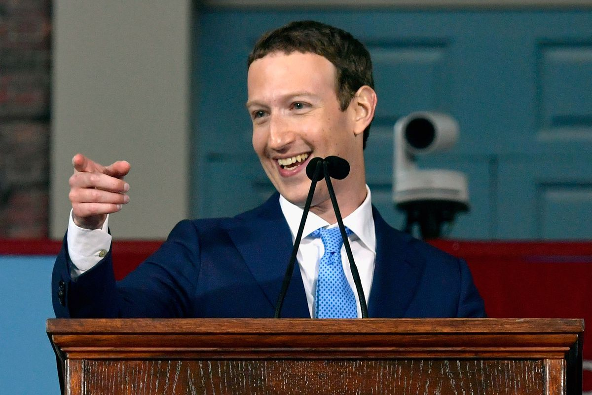Facebook CEO Mark Zuckerberg smiles and points from a podium where he is giving a speech.