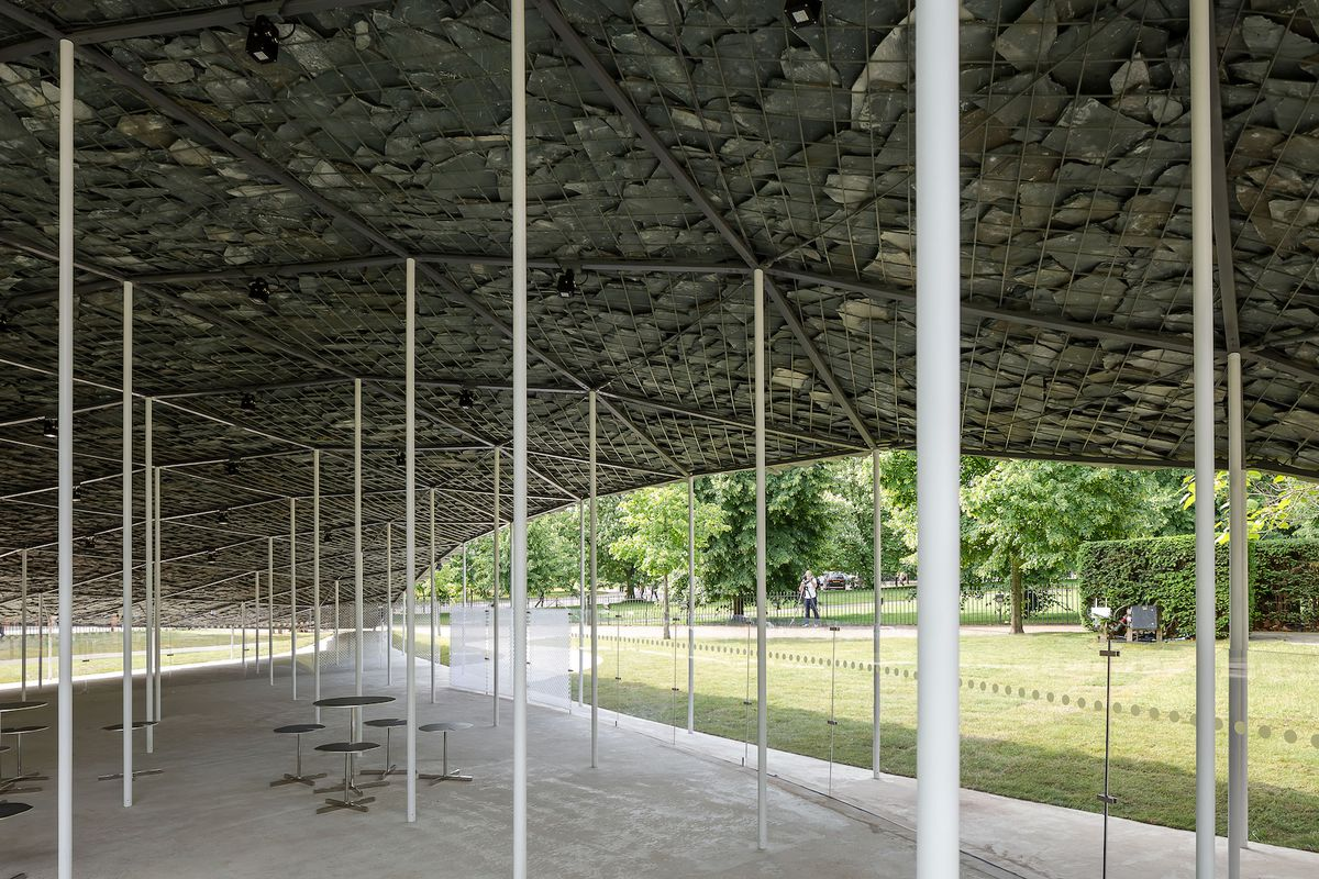 Tables and chairs under stone canopy
