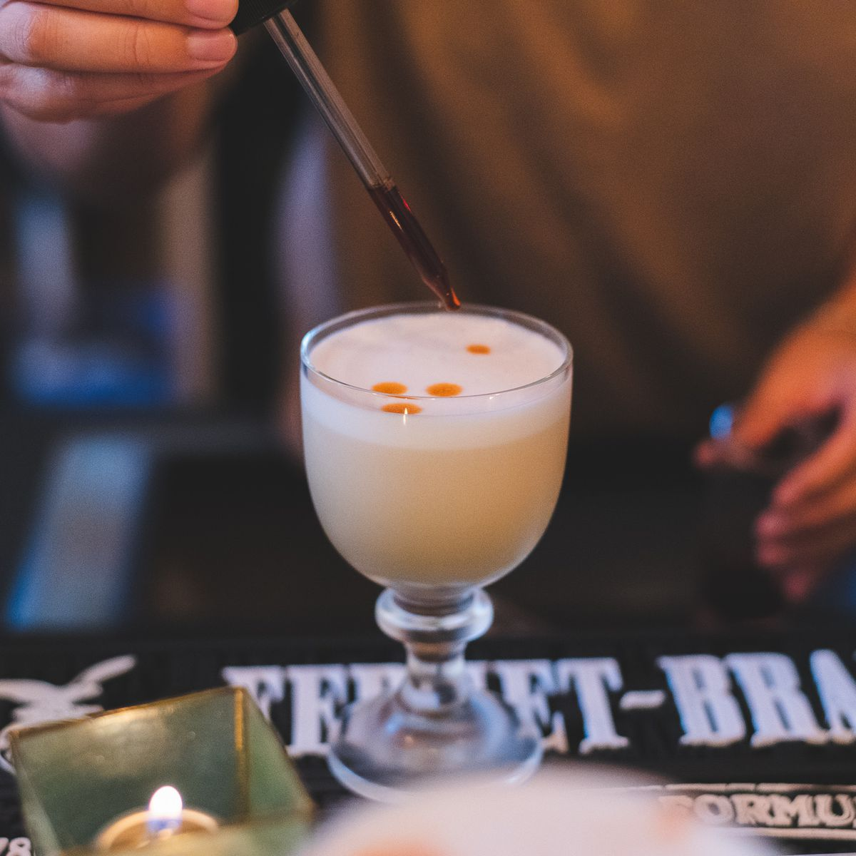 A bartender puts the finishing touches on a frothy calamansi sour at Hood Famous Cafe and Bar.