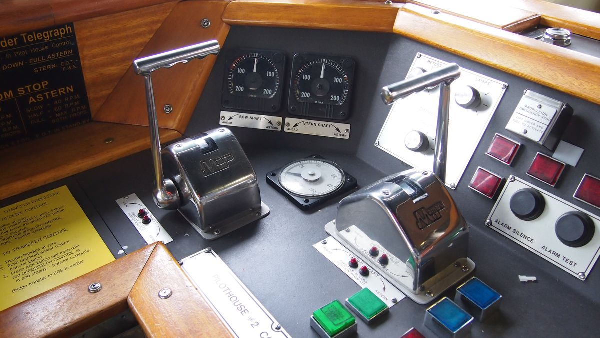 Levers, gauges, and buttons at the helm of a ferry