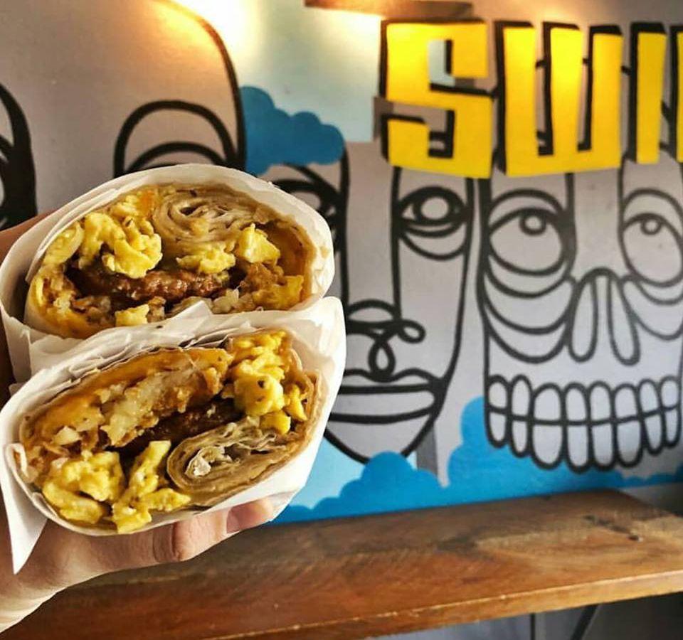 A breakfast burrito and sign at Chomp N' Swig