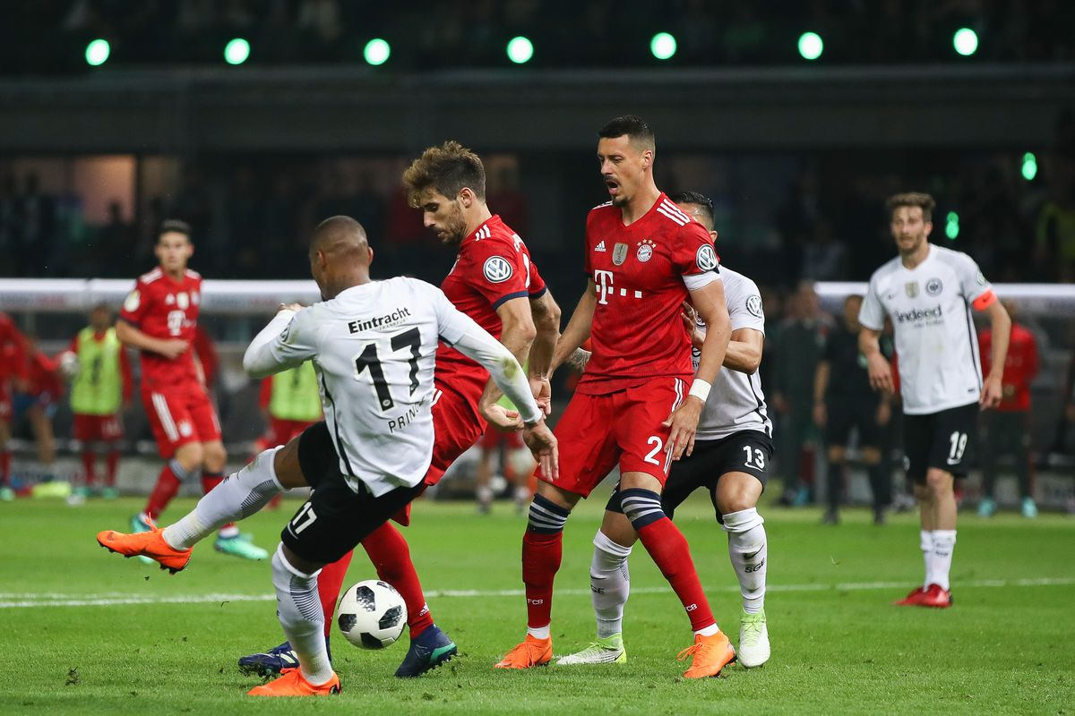 BERLIN, GERMANY - MAY 19: Javi Martinez #8 of FC Bayern Muenchen is challenged by Kevin-Prince Boateng #17 of Eintracht Frankfurt during the DFB Cup final between Bayern Muenchen and Eintracht Frankfurt at Olympiastadion on May 19, 2018 in Berlin, Germany.