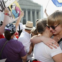 American University students Sharon Burk, left, and Molly Wagner, embrace outside the Supreme Court in Washington, Wednesday, June 26, 2013, after the court cleared the way for same-sex marriage in California by holding that defenders of California's gay marriage ban did not have the right to appeal lower court rulings striking down the ban.