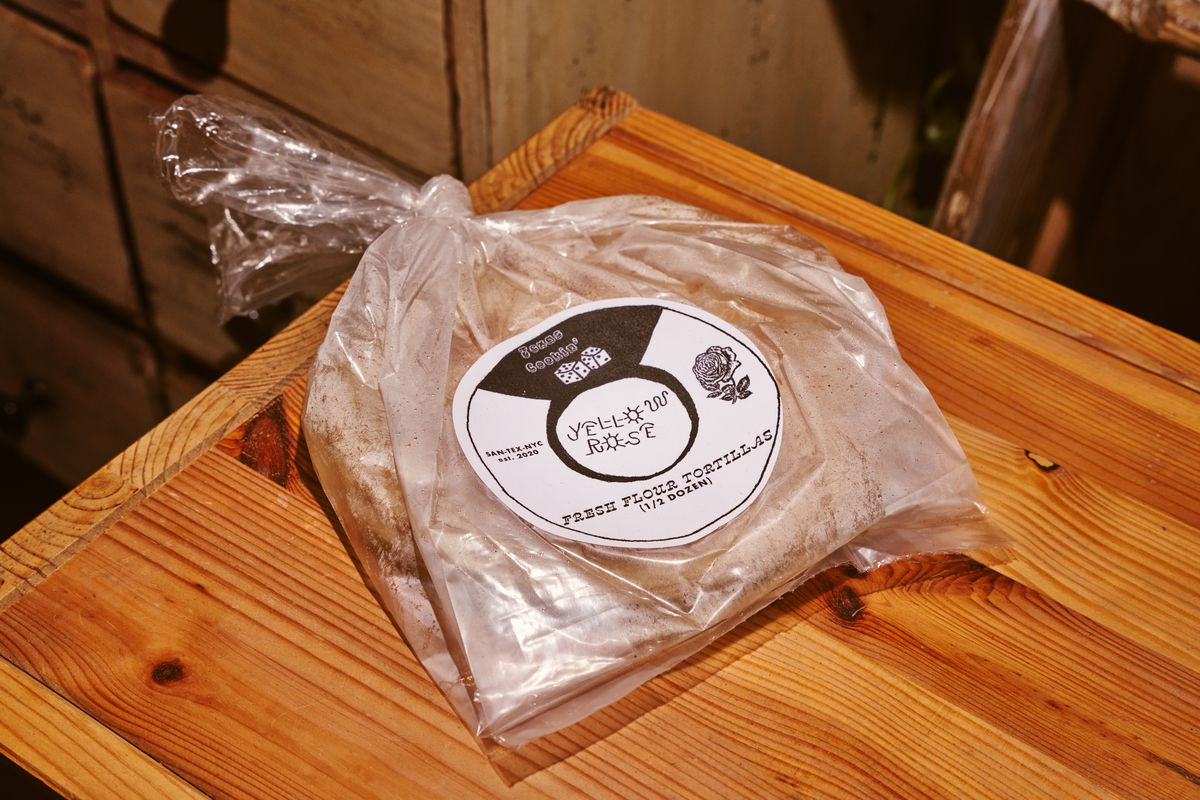 A package of packaged flour tortillas rests on a light brown wooden counter at a restaurant named Yellow Rose