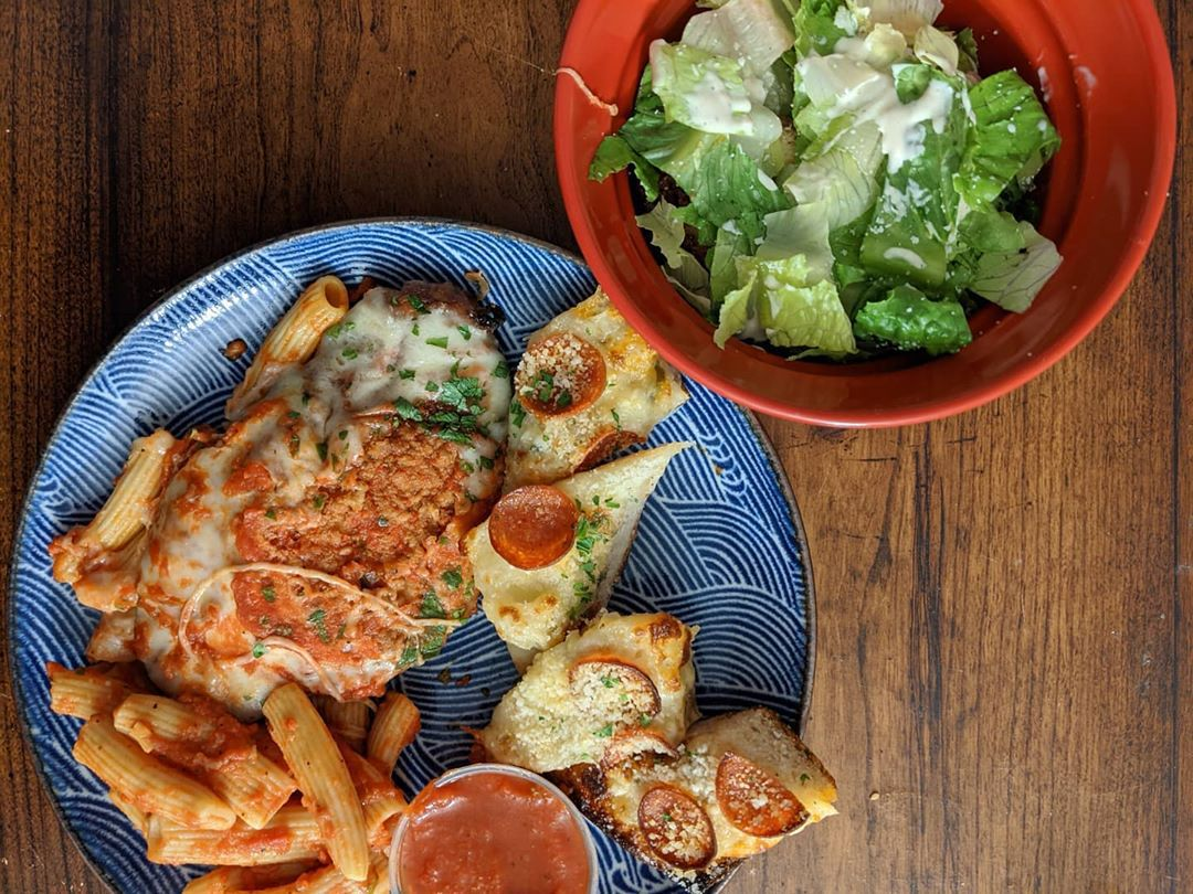 Overhead view of chicken parmesan and ziti on a blue plate, with a side of cheesy garlic bread topped with little pepperoni cups. A bowl of simple Caesar salad is to the side. All items are on a wooden tabletop.