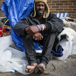 """""""Preach"""" sits on the sidewalk outside the Catholic Community Services (200 S. and 500 W.) next to the Road Home, called """"The Block,"""" in Salt Lake City on Wednesday, March 8, 2017. Preach was wearing shoes too tight which caused sores and for him to go without shoes in the cold which led to bad frostbite on his toes."""