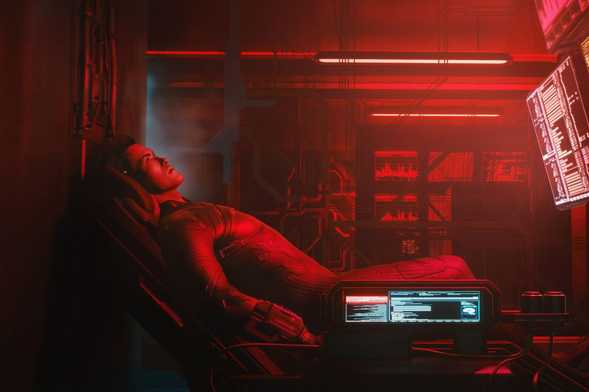 An NPC sits in front of a computer terminal, bathed in red light.