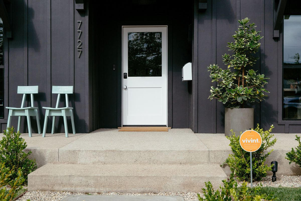 Close-up of the front of a house with a Vivint sign in front of it