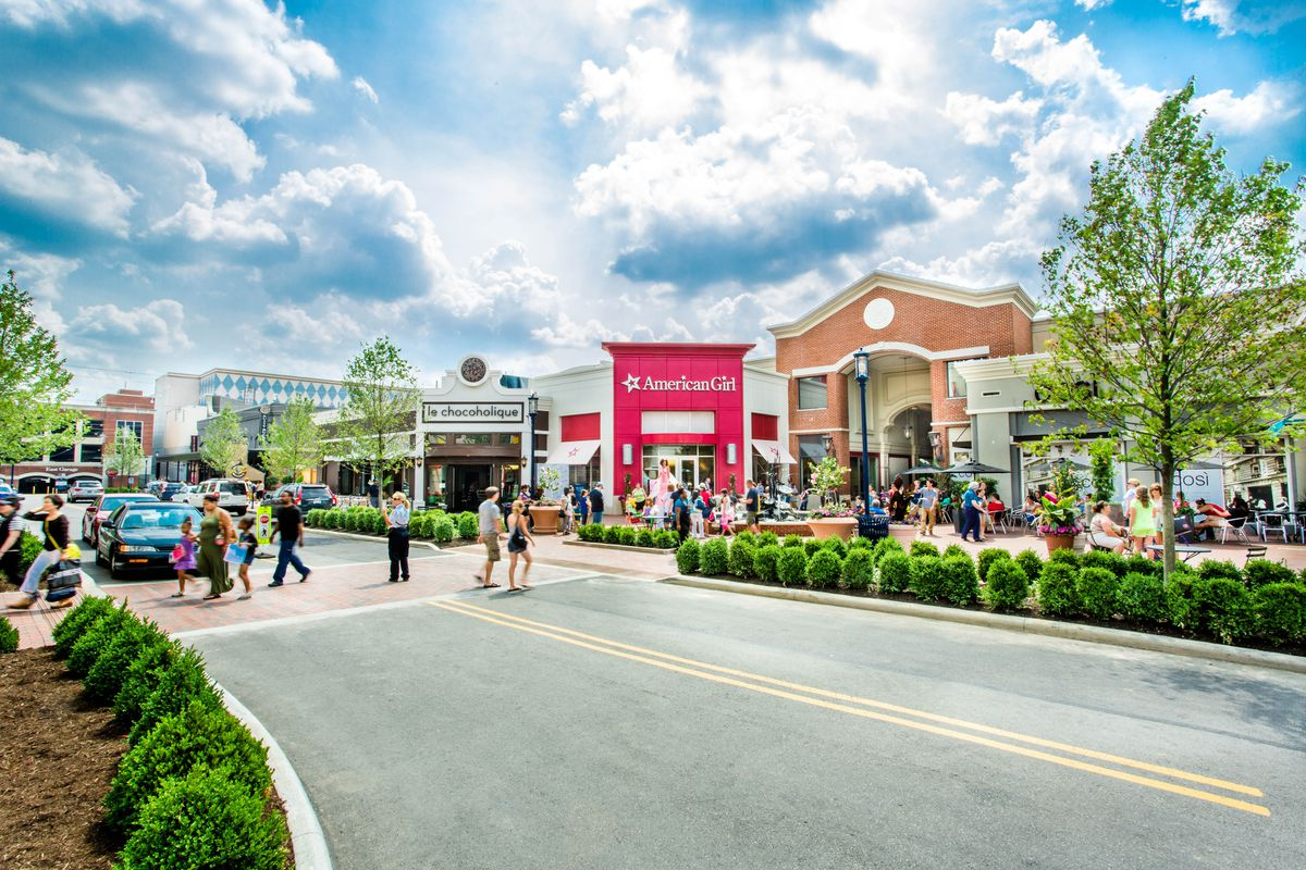 Some shoppers cross a street at Easton Town Center to an American Girl store, while others sit and eat a Cosi.