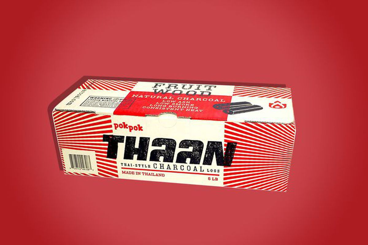 A box of Thaan charcoal logs on a red background