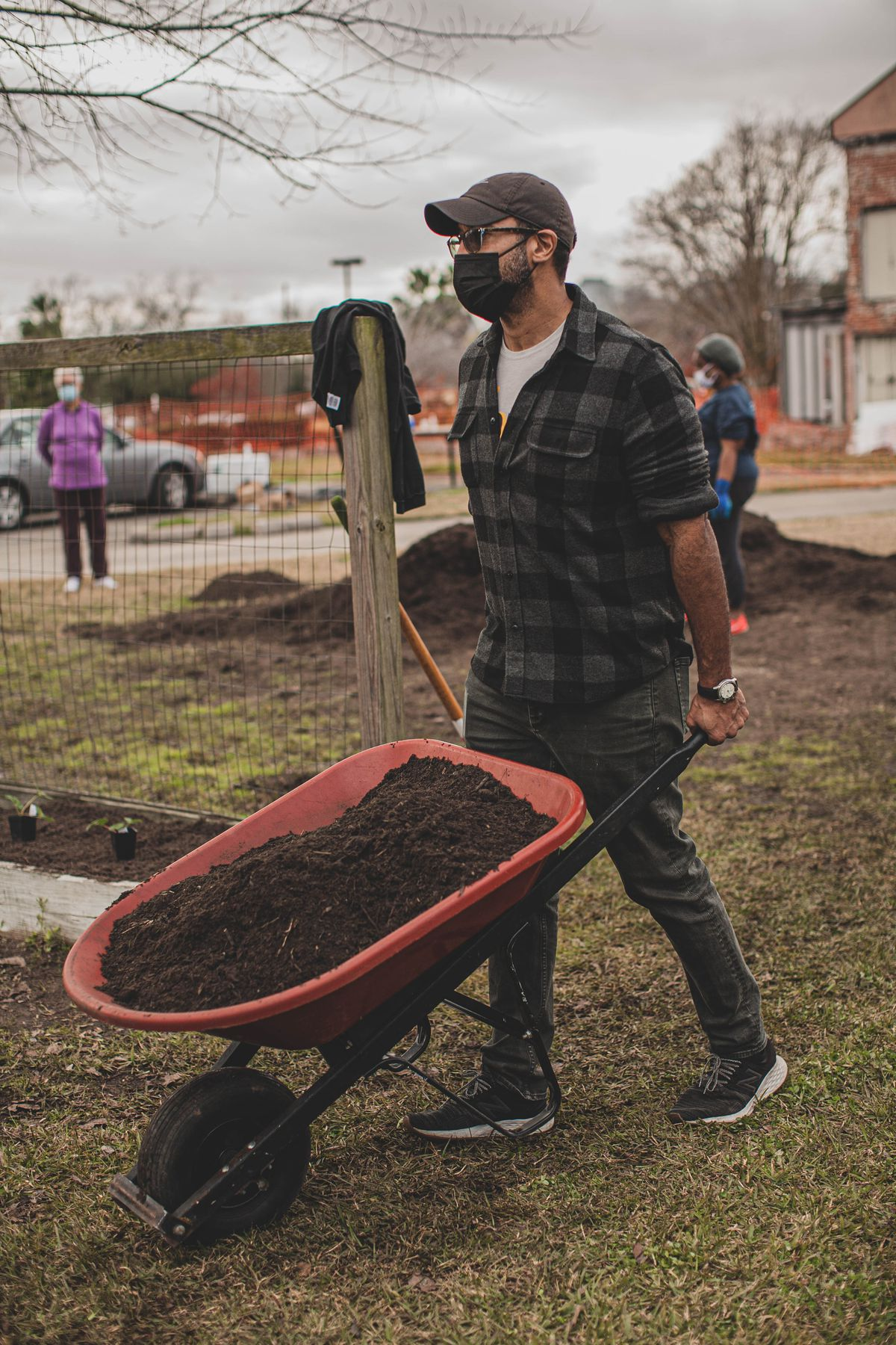 A man wearing a black masks pushes a red wheelbarrow full of soil.