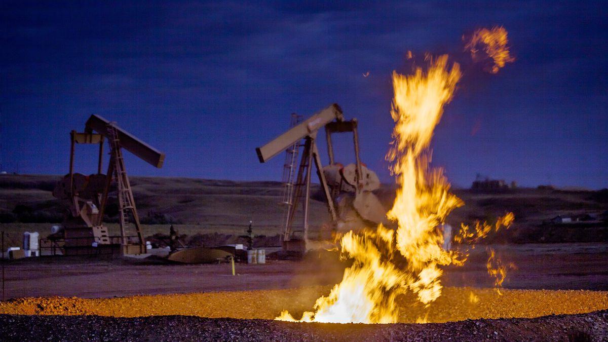 A fire burns in a pit beside oil pumps in an oil field.