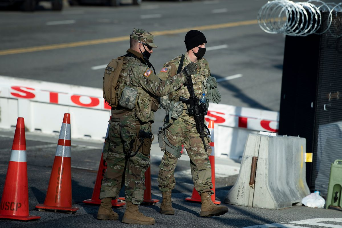 Two National Guards in camouflage and carrying guns stand on a street line with concrete barricades and orange traffic cones.