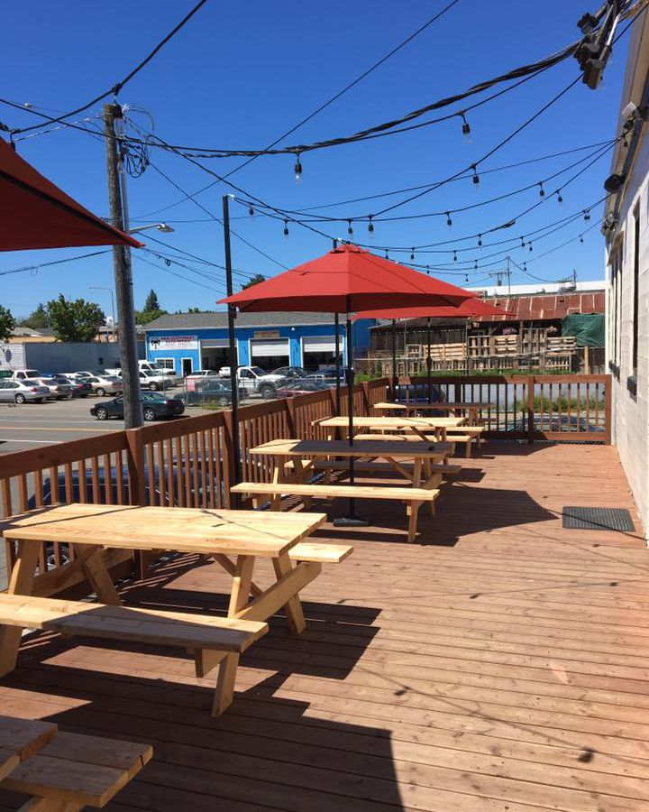 Picnic tables on the patio at Beer Star on a sunny day, with orange umbrellas and strings of lights.