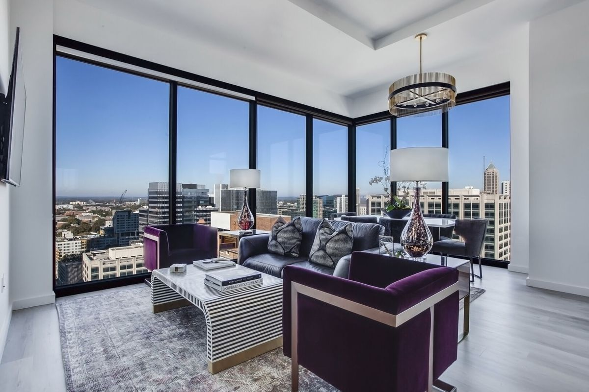 A penthouse with purple chairs and big windows in Atlanta.