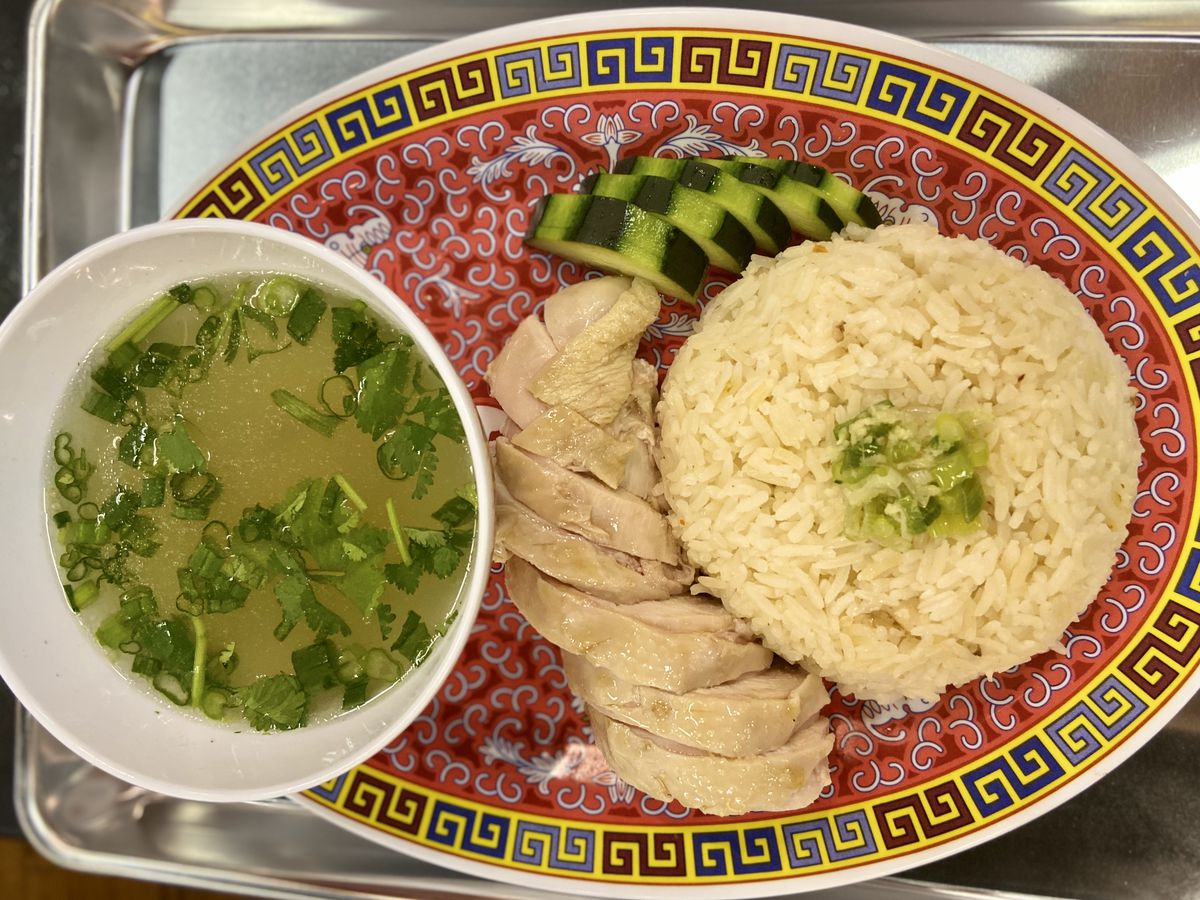 Sliced chicken, rice, and a bowl of broth on a red plate