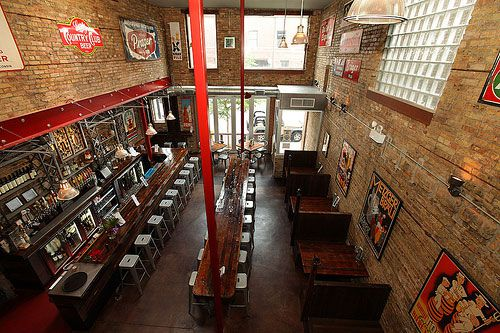 An aerial shot of a large bar with exposed brick walls and a tall red pole coming down from the ceiling.