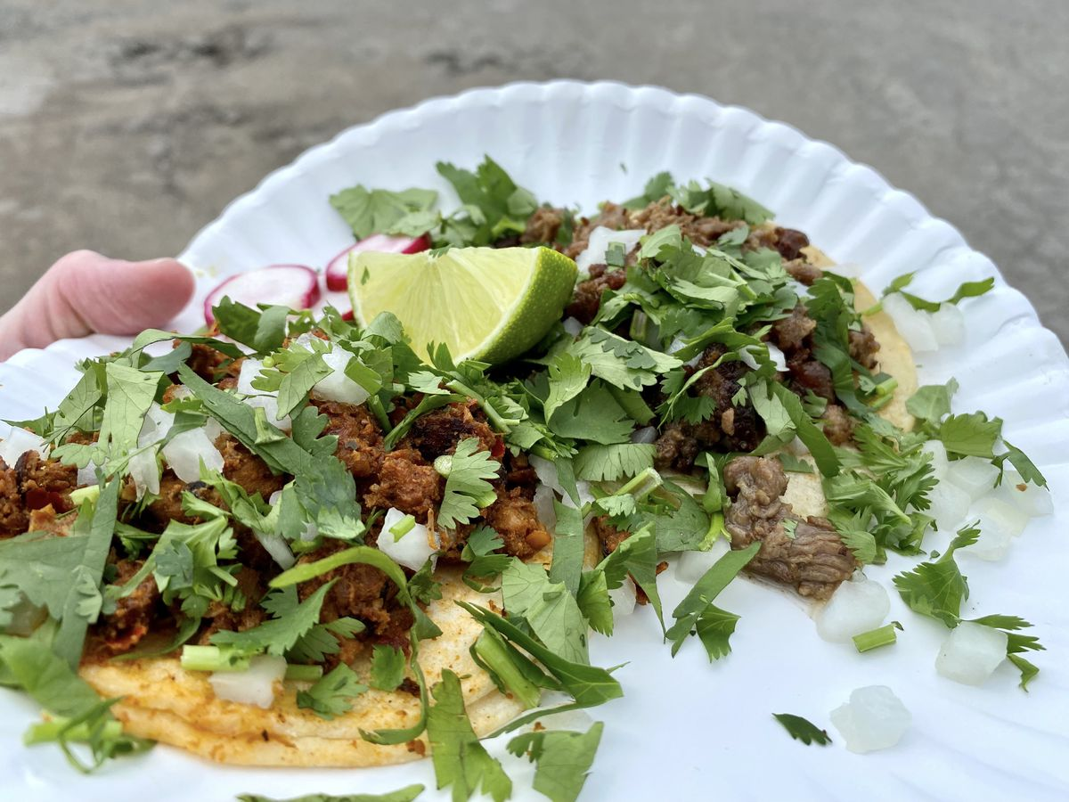 A hand holds two paper plates of tacos overflowing with herbs, radishes, and a lime wedge, with meat peaking out from below