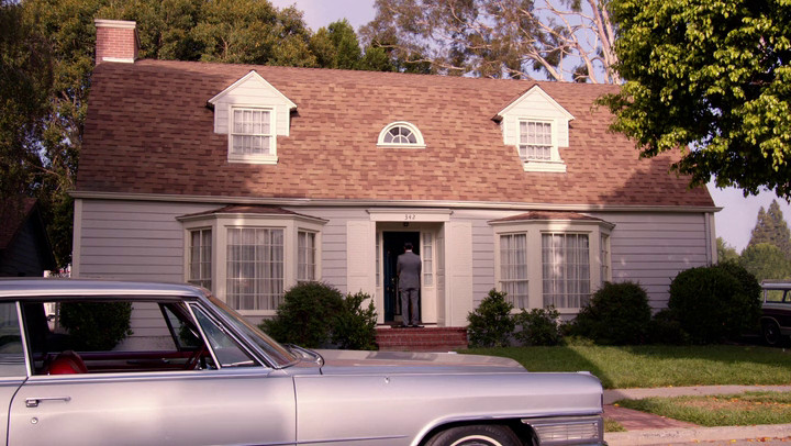 Don waits outside a house he might have put in an ad on Mad Men.