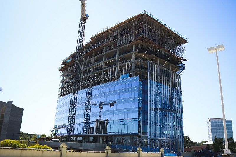 A glassy mid-rise building with a crane beside it and open floors still being built.