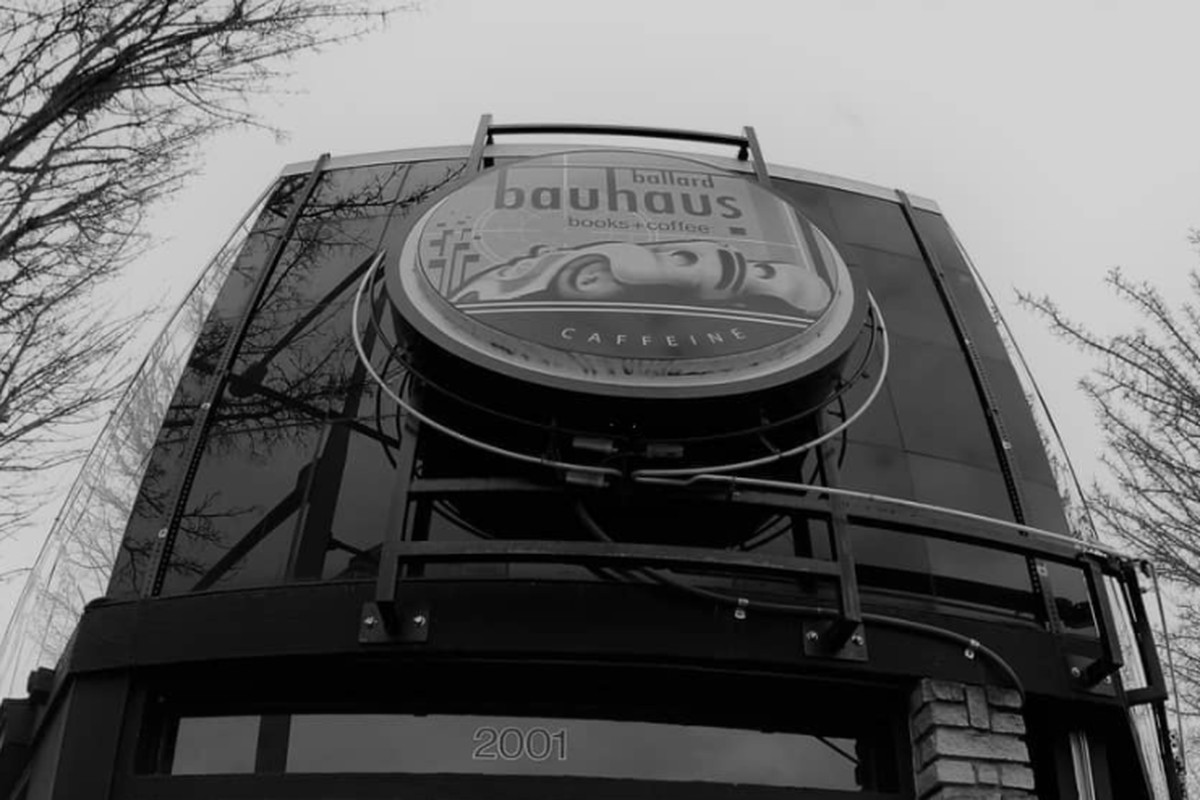 A black-and-white photo of the storefront for Bauhaus Strong Coffee, with the cafe's sign shown from a low-angle perspective