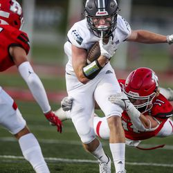 Corner Canyon's Jon King (14) runs as American Fork's Kyle Moore (11) tries to stop him at American Fork High School on Friday, Sept. 17, 2021.