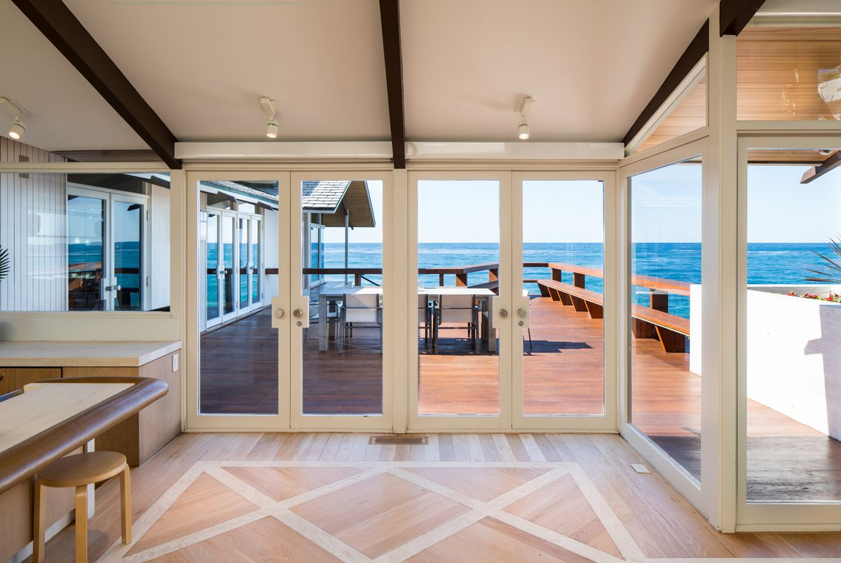 Two sets of white doors open up on to a wooden deck with an outdoor table by the ocean.