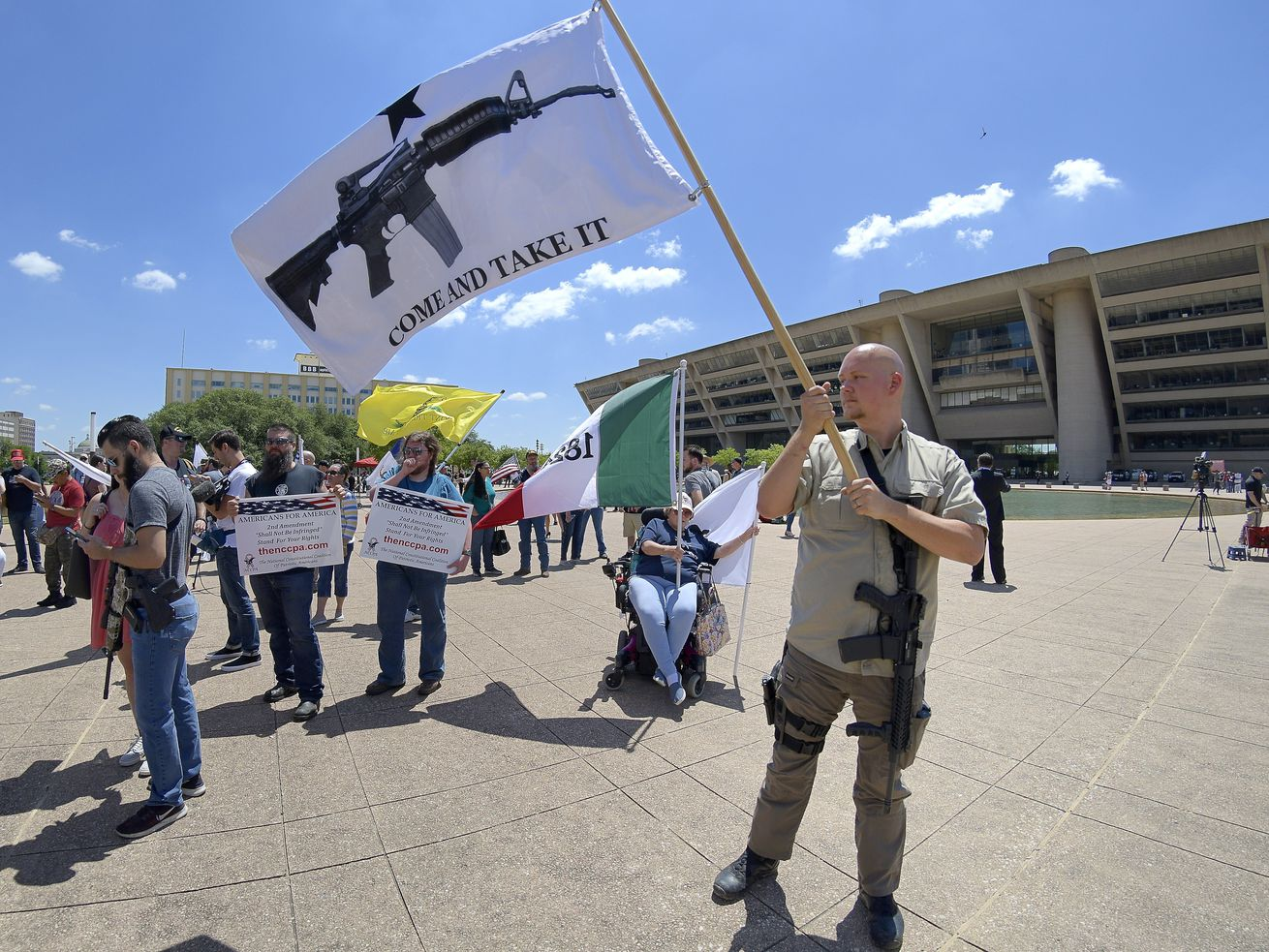 """A man with an AR-15 slung over his shoulder waves a flag depicting an assault rifle along with a message that reads """"Come and take it."""""""