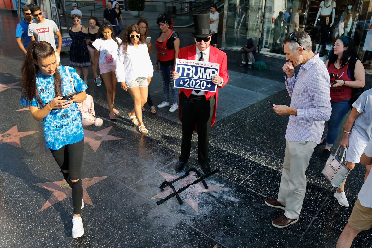 A man stands with a Trump 2020 sign near the president's star on the Hollywood Walk of Fame in July 2018.