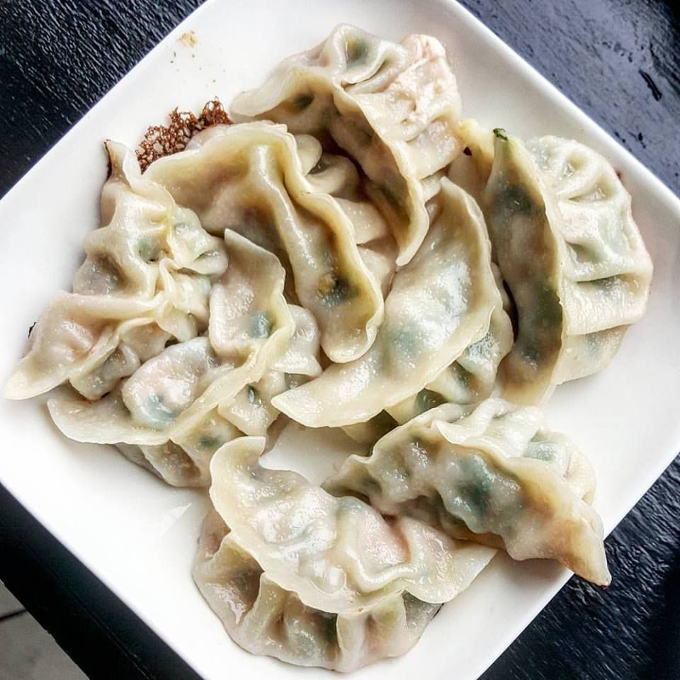 Overhead view of a square white plate covered with steamed, pleated dumplings