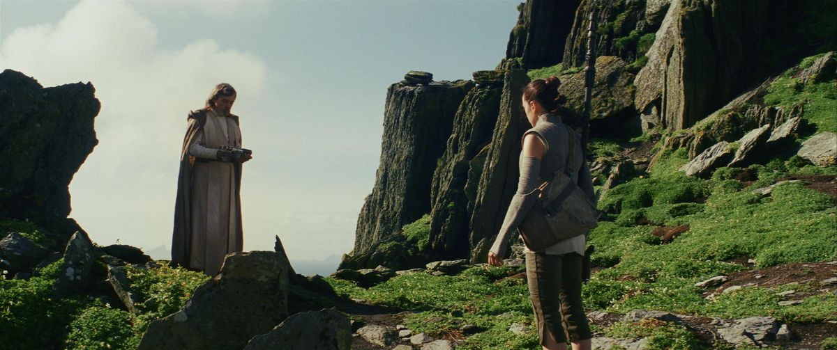 Rey looks at Luke holding his lightsaber on Ahch-To in Star Wars: The Last Jedi