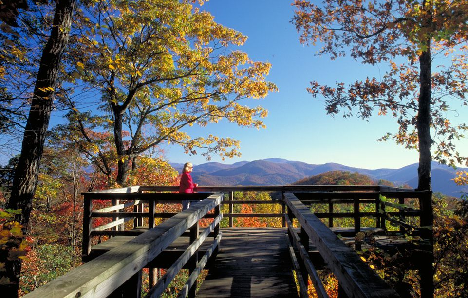A wooden bridge leading to a lookout deck. The deck is surrounded by trees with colorful leaves. There are mountains in the distance.