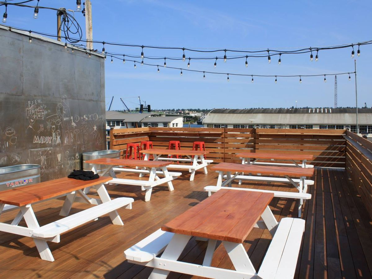 A series of picnic tables at Rooftop Brewing Company on a clear, sunny day