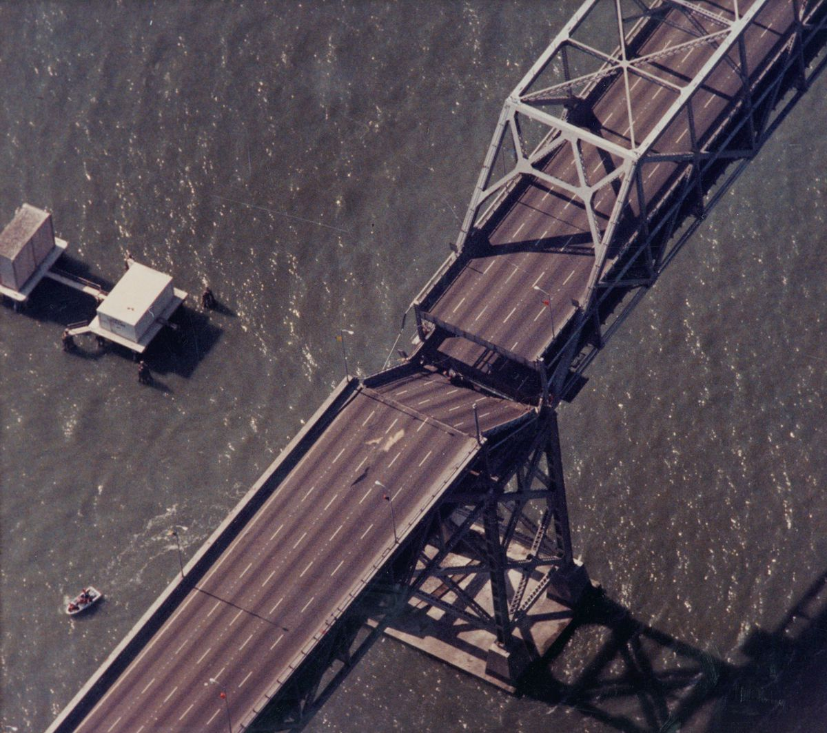 An aerial shot of a bridge with a chunk fallen down onto the lower deck.