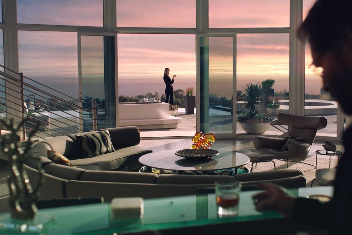 Renata Klein's living room on the television show Big Little Lies. There is a couch, table, and armchair in the foreground. In the distance is a wall of windows looking out onto a pink and purple toned sunset..