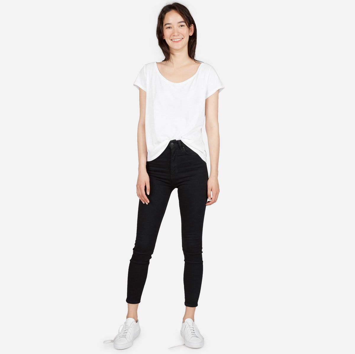 A model in a white T-shirt and black jeans
