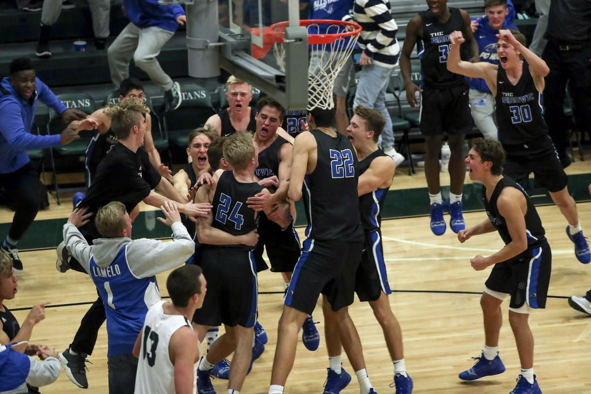 Pleasant Grove players mob teammate Kael Mikkelsen, center, after he made a shot at the buzzer to defeat Olympus at Olympus High School in Holladay on Tuesday, Nov. 27, 2018.