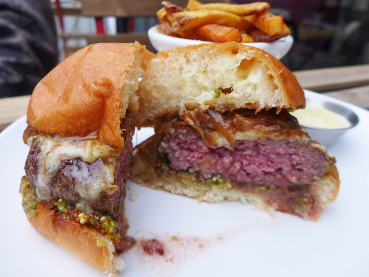 A burger cut in half with a puffy brioche bun and green relish, with aioli and fries in the background.