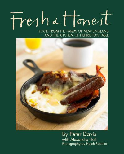 A cookbook cover features a dark green border and a cast iron breakfast skillet of eggs, bacon, sausage, and more. A mug of coffee and glass of orange juice are visible in the background.